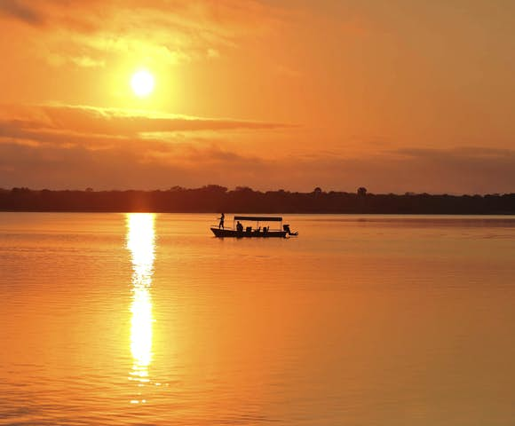 Sunset over lake with boat on river at Selous Game Reserve, Tanzania
