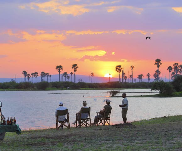 People sitting in front of lake with sunset, Selous Game Reserve