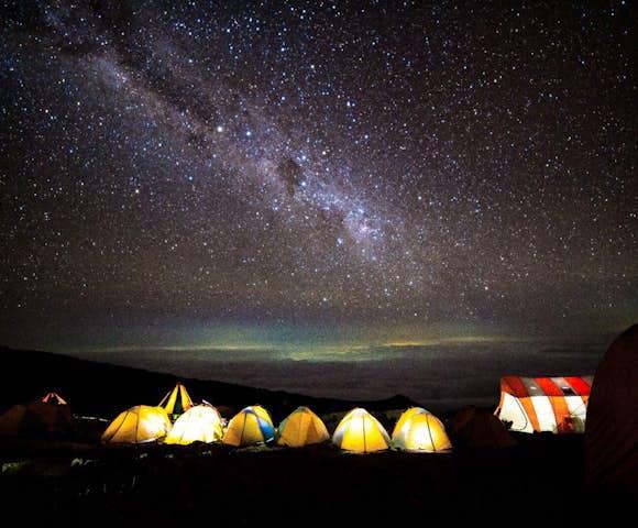 Night sky above glowing tents on Kilimanjaro hike in Tanzania